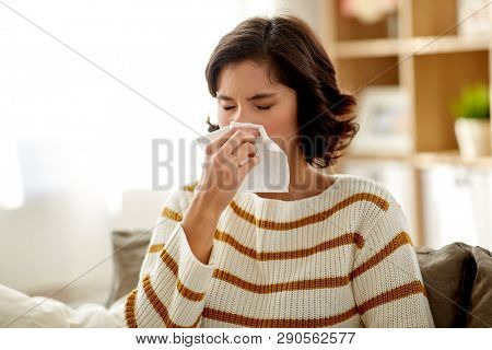 healthcare, cold, allergy and people concept - sick woman blowing her runny nose in paper tissue at home
