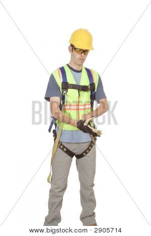 Construction Worker In Climbing Harness Puts On Gloves.
