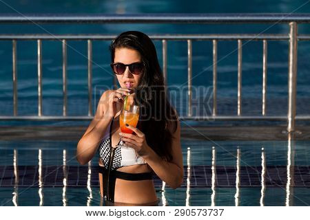 Pretty Woman With Long Dark Hair Wearing A White Swim Suit Drinking A Cocktail Standing In A Pool Wi