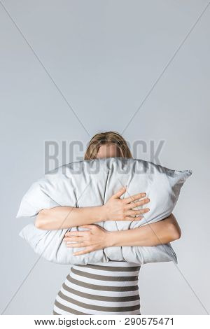Young Woman Hugging A Gray Pillow, Hiding Her Face Behind It.
