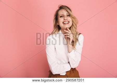 Portrait of gorgeous blond woman 30s in stylish outfit smiling and looking at camera isolated over red background poster