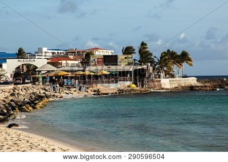 SINT MAARTEN - JULY 31, 2015: Famous Maho Bye Beach area with water side and Sunset Bar and Grill restaurant in St.Maarten near Princess Juliana International Airport.