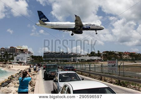 MAHO BAY BEACH, ST MAARTEN -  AUGUST 01, 2015: Airplane Jet Blue is landing on Princess Juliana International Airport, over famous Maho Bay Beach.