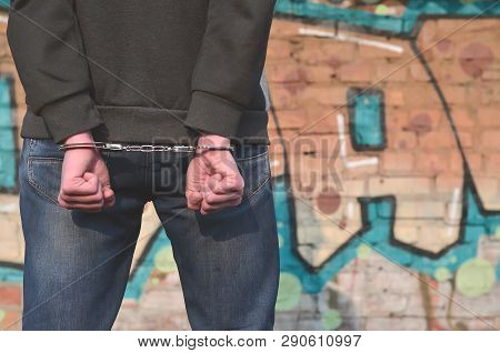 Rear View Of The Arrested And Handcuffed Offender Against The Gr