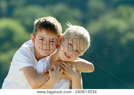 Two Little Boys Are Hugging Outdoors. Concept Of Friendship And Fraternity.