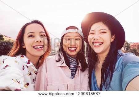 Happy Asian Girls Taking Selfie With Mobile Smartphone Outdoor - Young Social Friends Having Fun Tak