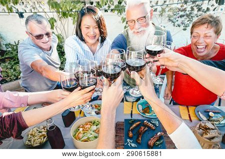 Happy Senior Friends Toasting With Red Wine Glasses At Dinner Time Outdoor - Mature People Having Fu