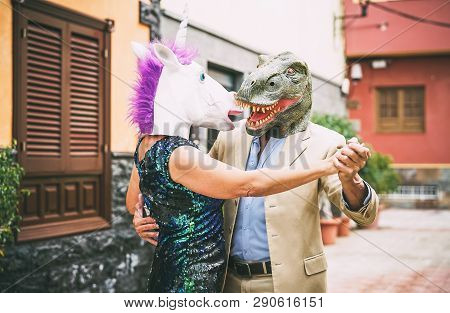 Crazy Couple Dancing And Wearing Dinosaur T-rex And Unicorn Mask - Senior Elegant People Having Fun