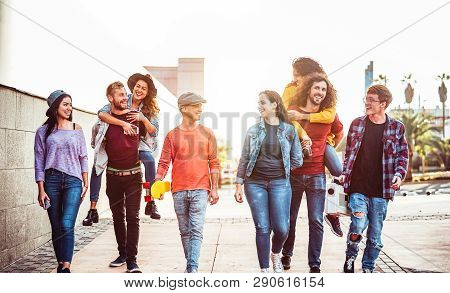 Group Of Happy Friends Having Fun Outdoor - Young People Piggybacking While Laughing And Walking Tog