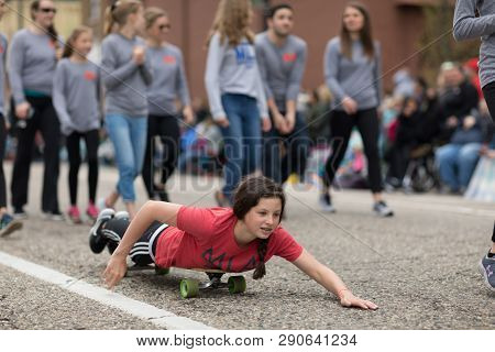 Holland, Michigan, Usa - May 12, 2018 Young Woman Pretends To Be Swiming On Top Of A Skateboard, Goi