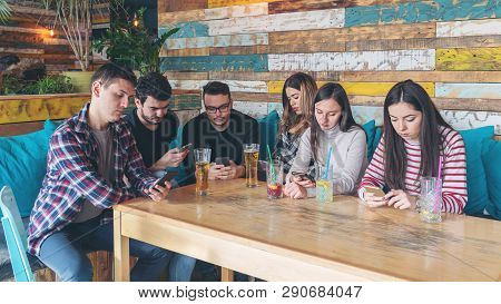 Group Of Friends At Restaurant Ignoring Each Other In Favour Of Mobile Phone - Young People Addicted
