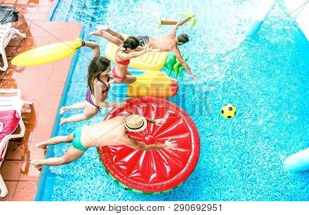High angle view of millenial friends jumping at swimming pool party - Youth vacation concept with happy guys and girls having fun in summer day at luxury resort - Young people on warm bright filter poster