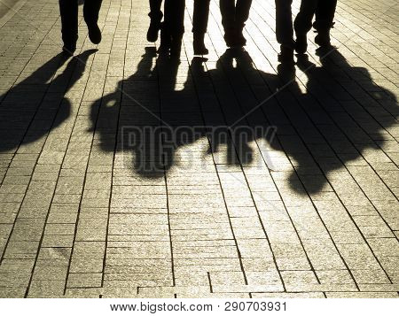People Silhouettes And Shadows On The Street. Crowd Walking Down On Sidewalk, Concept Of Strangers,