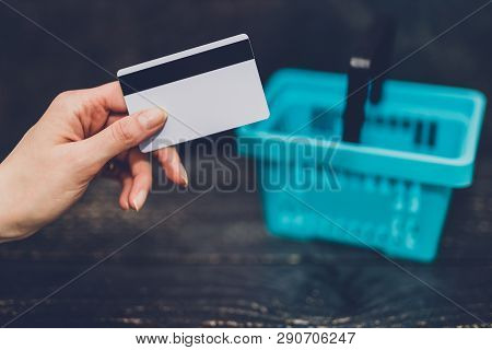 Hand Holding Payment Card With Shopping Basket Next To It