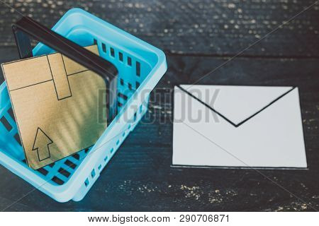 Email Marketing Concept: Shopping Basket With Parcel Inside And Email Envelope Next To It