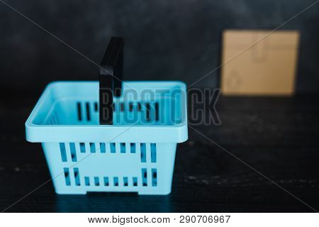 Add To Cart Concept: Empty Shopping Basket With Cardboard Delivery Parcel In The Distance