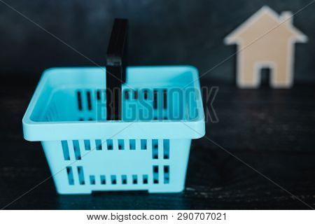 Buying Decor Items Or Furniture Concept: Shopping Basket And Small Cardboard House Next To It