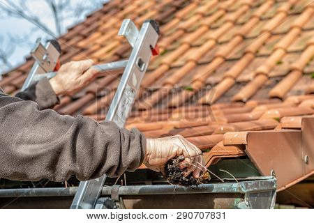 Man On A Ladder Cleaning House Gutters