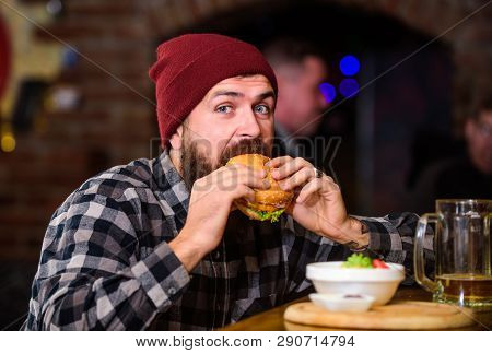 Brutal Hipster Bearded Man Sit At Bar Counter. High Calorie Food. Cheat Meal. Delicious Burger Conce