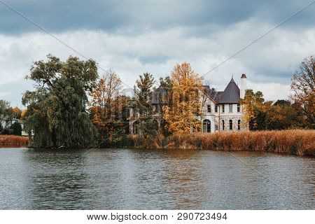 Landscape Nature View Of Beautiful Erupean Gothic Looking House Castle Hidden Behind Trees Near Pond