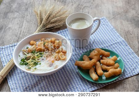 Breakfase Meal. Congee Or Rice Porridge Minced Pork, Boiled Egg With Soy Milk And Chinese Deep Fried