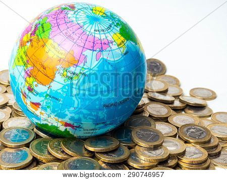 Pile Of Coins With World Planet On The Background - Concept Of Saving The Planet, Concept Of Relatio