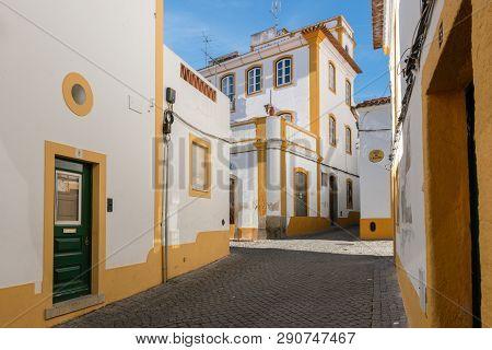 The View Of Narrow Paved Street Of Evora With The Cozy White Houses. Evora. Alentejo. Portugal