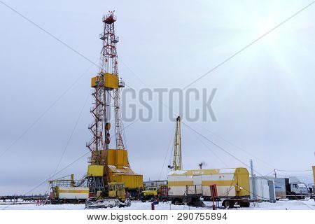 Silhouette Image Of Oil And Gas Drilling Rig In The Middle Of Nowhere With Dramatic Sky. Onshore Lan