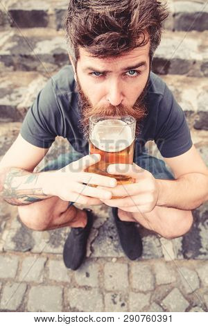 Guy Having Rest With Draught Beer. Man With Beard And Mustache Holds Beer While Sits On Haunches, St