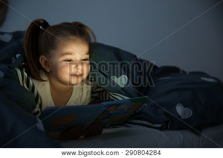 Beautiful little girl reading book in bed at night. Bedtime story poster
