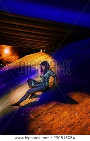 Attractive girl in futuristic clothes on a concrete structure. Space stylization