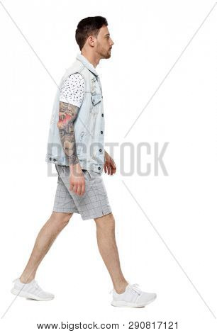 Back view of going  handsome man in a shorts. walking young guy . Rear view people collection.  backside view of person. Isolated over white background. A guy with a tattoo in shorts walks by.