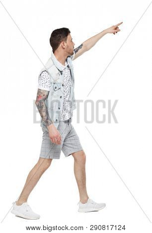 Side view of a man walking with a pointing hand. going  guy showing.  backside view of person.  Rear view people collection. Isolated over white background. Tattooed guy goes showing thumb up.