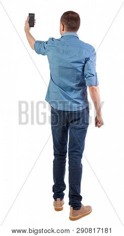 Back view of man who makes selfie with a smartphone. guy watching. Rear view people collection.  backside view of person. Isolated over white background. The guy in the shirt makes a selfie.