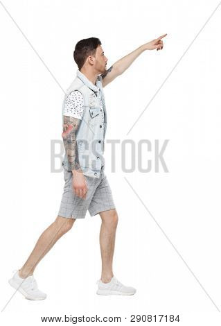 Side view of a man walking with a pointing hand. going  guy showing. Rear view people collection. Isolated over white background. A guy with a tattoo in shorts passes showing his hand up.