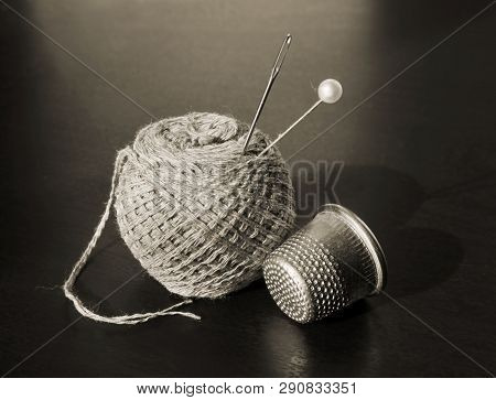 Still Life With Vintage Thimble, Thread, Pin And Sewing Needle In Sepia Tone Against A Low Key Backg