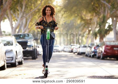 Full length shot of millennial black woman riding an electric scooter in the street
