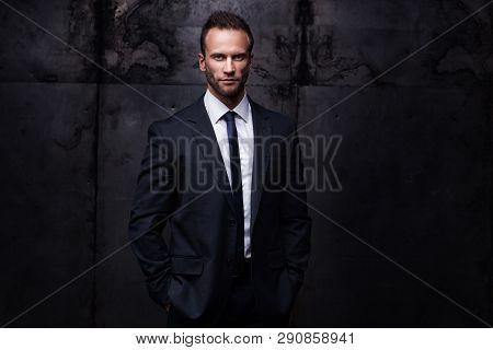 Portrait Of Young Handsome Businessman Isolated On Dark Grunge Studio Background
