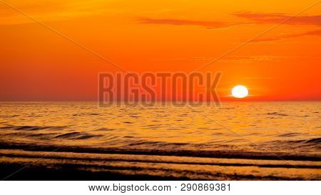 Idyllic Shot Of Sunset By The Sea Waters, Warm, Orange And Red Colors.
