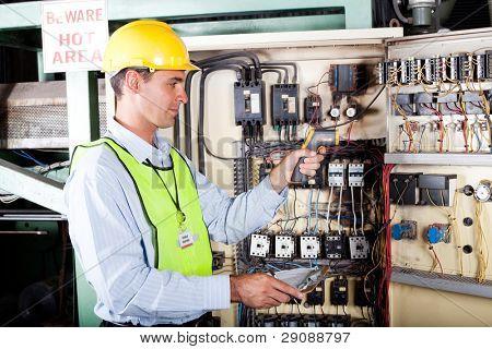 männlich caucasian Elektriker überprüfen industrielle Maschine Steuerelement Feld Temperatur