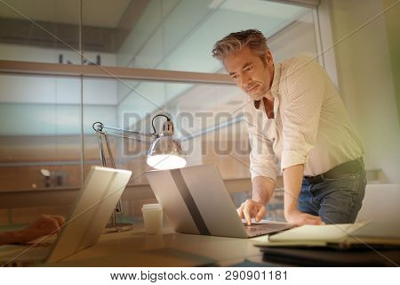Mature businessman working late in modern office