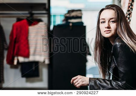 89753d8a82c1 The young pretty woman choosing, trying and buys dresses at shop clothing.  Banner for online store clothing. Girl posing in fashionable clothes