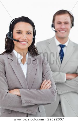 Smiling call center agents with headsets and arms folded against a white background