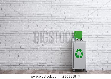 Overfilled Trash Bin With Recycling Symbol Near Brick Wall Indoors. Space For Text