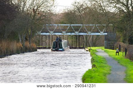 Two Men Drive A Boat Down A Narrow Canal In Rural Shropshire, England.