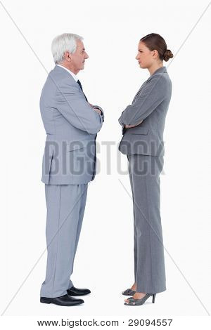 Businesspartner standing face to face with arms folded against a white background