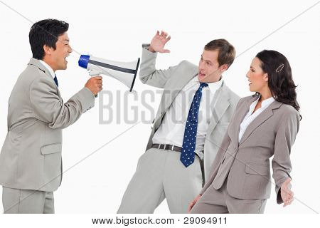 Businessman with megaphone yelling at colleagues against a white background