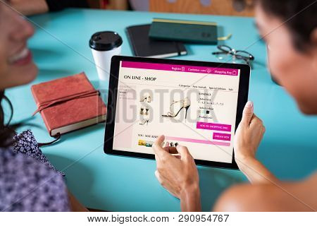 Closeup of woman doing online shopping on digital tablet at cafeteria. Woman buy elegant shoes on online market website. Back view of two girls using digital tablet to shop online.
