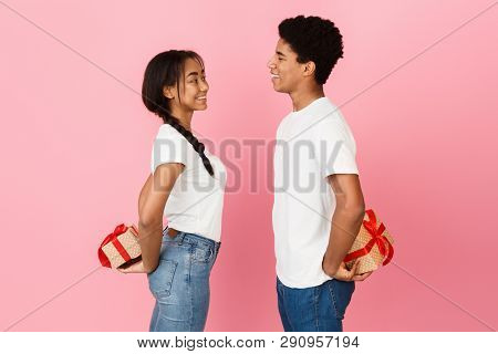 Happy Teen Couple Hiding Gift Boxes Behind Backs Over Pink Background, Side View