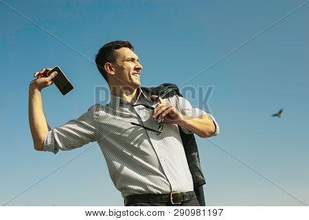 Happy Stunning Man Throwing Away His Phone